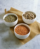 Dried green and red lentils and chick-peas in small bowls