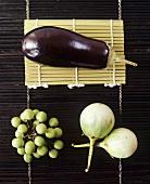 Drei verschiedene Auberginensorten auf Bambusmatten