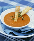 A plate of carrot soup with fresh thyme and bread sticks