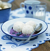 Blueberry and coconut dumplings on blueberry sauce