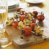 Grilled tomato and mushroom kebabs on a wooden board