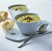 Cream of asparagus soup in two bowls with baguette