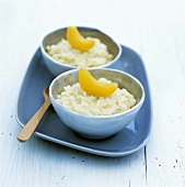 Two bowls of coconut rice pudding with peach