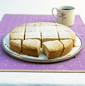 Plain cake with icing sugar, cut into pieces, on cake plate