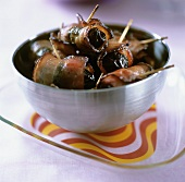 Bacon-wrapped prunes in a small bowl