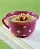 A cup of pea soup with fried ham