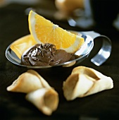 Chocolate cream with orange wedge and wafers