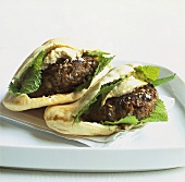 Two pita breads filled with lamb burgers, hummus and mint