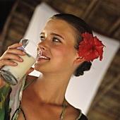 Junge Frau in Strandkleidung hält einen Drink in der Hand