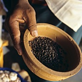 Man holding terracotta bowl of black peppercorns