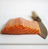 A piece of raw salmon with a knife