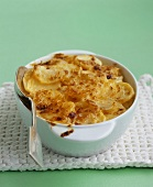 A dish of potato gratin with a spoon