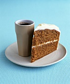 A piece of carrot cake with cream cheese icing, coffee