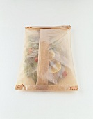Wolfsbarsch mit Gemüse in Pergemantpapier eingepackt
