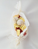 Mango with raspberries and coconut balls in baking parchment
