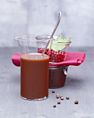 Venison gravy in a glass beaker, spices and preserving jar