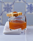 Jar of apricot jam with a slice of buttered brioche
