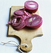 Partly sliced red onion on a chopping board