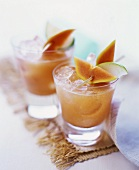 Two glasses of papaya and apple juice with ice cubes