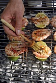 Brushing prawn kebabs on a barbecue