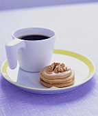 A cup of coffee with a walnut biscuit