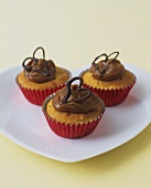 Three banana cupcakes with dulce de leche topping