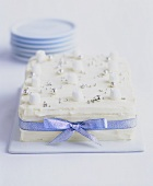 White coconut cake with silver dragées and ribbon