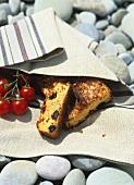 Angeschnittener Schinkenkuchen auf Küchentuch und Steinen