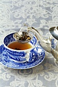 A cup of tea with silver teapot and tea strainer