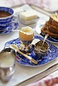 Frühstückstablett mit Frühstücksei, Salz, Brot, Butter, Tee