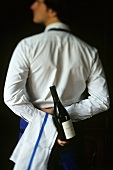 Sommelier with a bottle of wine behind his back