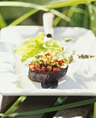 Marinated aubergine slices with diced peppers and herbs