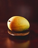 A mango on a wooden plate