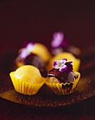 Mango truffles with chocolate sauce in petit four cases
