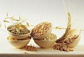 Getreidekröner und Linsen in Schälchen mit Ähren