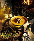 Cream of pumpkin soup with wild mushrooms in front of a fire