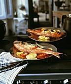 Two red mullet with vegetables and sage on range