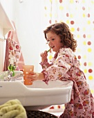 Little girl in bathrobe brushing her teeth