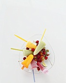 Ice lollies on fruit in a glass dish