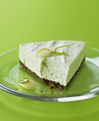 A piece of lime cheesecake with chocolate biscuit base
