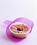 Muffin with iced flower and gift ribbon