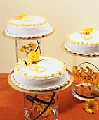 Three white cakes with fondant icing and springtime decorations