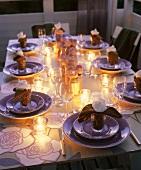 Romantisch gedeckter Tisch mit Teelichten am Abend