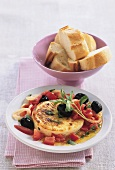 Fried goat's cheese with tomatoes, olives and baguette