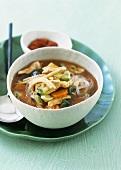 Sauer-scharfe asiatische Suppe mit Gemüse und Hähnchenbrust