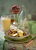 Muesli with apple and a glass of orange buttermilk