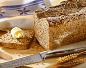 Roggen-Sauerteig-Brot, angeschnitten mit Butter