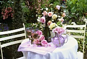 White wine and summer flowers on a garden table