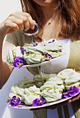 Young woman carrying pistachio meringues on tiered stand