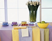 Table with pastel-coloured crockery and table linen